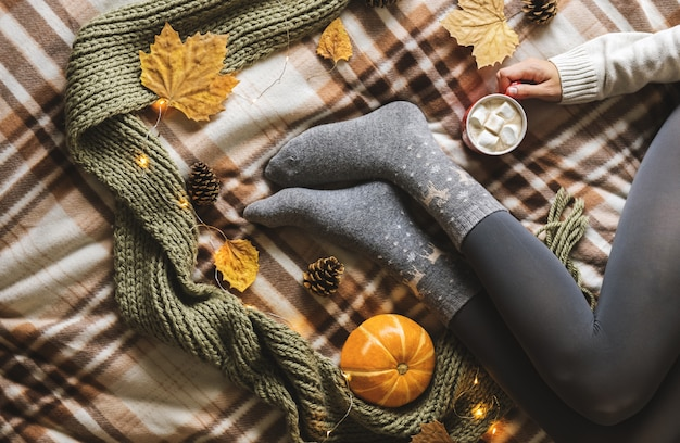 De handen en voeten van vrouwen in wollen grijze sokken die een kop warme koffie met marshmallow houden