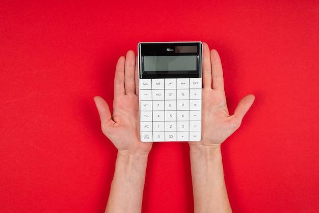 De handen houden een calculator die op rode achtergrond wordt geïsoleerd