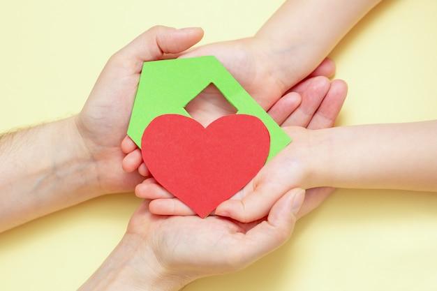 De handen houden groenboekhuis met rood hart.