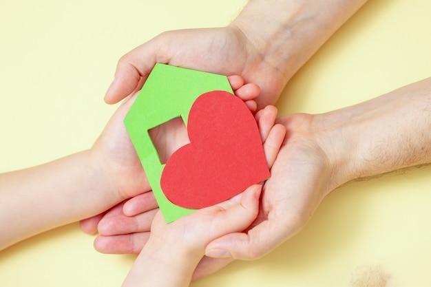 De handen houden groenboekhuis met rood hart