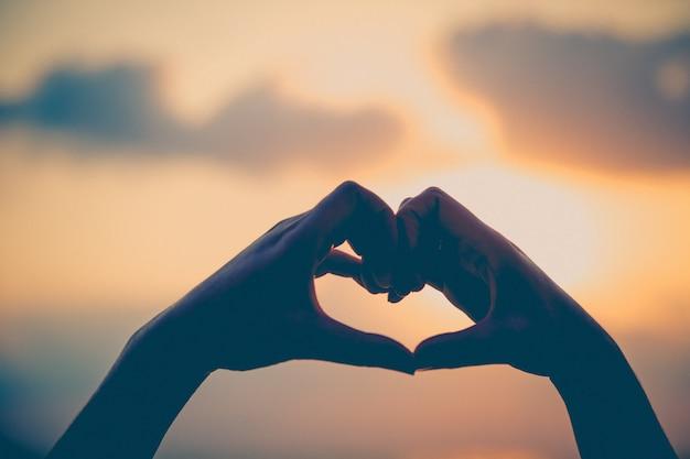 De handen maken in de liefde van de hartliefde met silhouet bij zon vastgestelde achtergrond