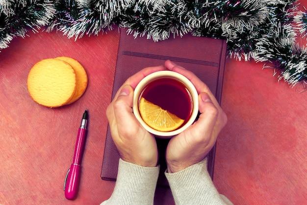 De handen met een kopje thee op de kantoortafel voor het nieuwe jaar