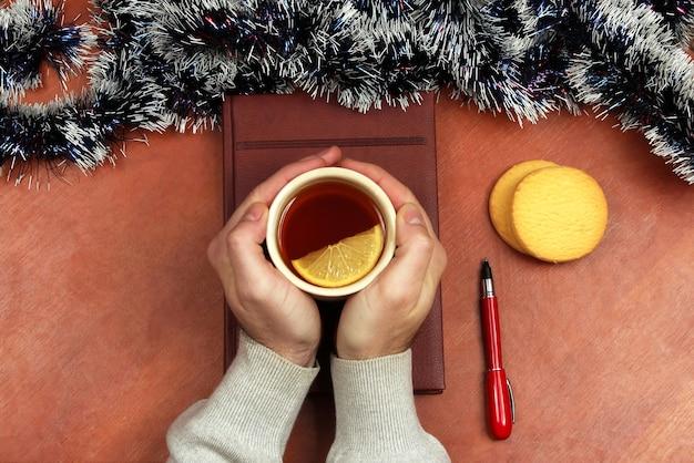 De handen met een kopje thee op de tafel op kantoor voor de kerst