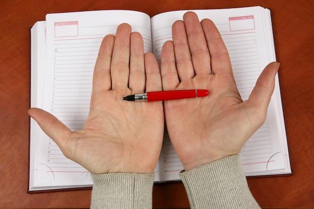 De handen met een rode pen boven een opengeslagen notitieboekje