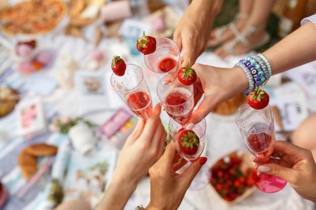 De handen met glazen juichen op picknick van de de zomerdag toe