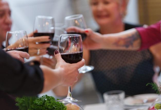 De handen met glazen rode wijn sluiten omhoog.