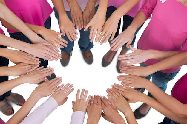 De handen sloten zich in cirkel aan die roze voor borstkanker dragen op witte achtergrond