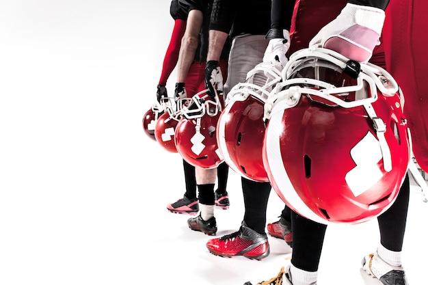 De handen van amerikaanse voetballers met helmen
