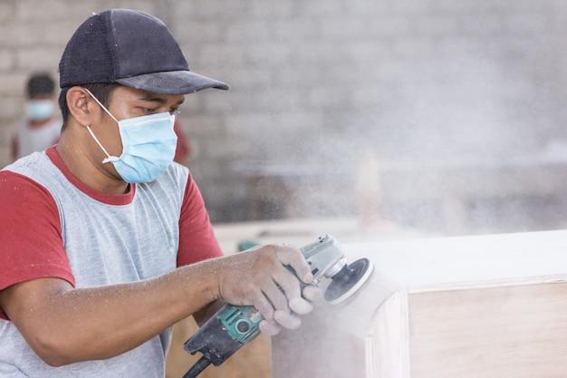 De handen van arbeiders bij timmermanswerkruimte die de oppervlakte van hout verfijnt
