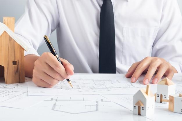 De handen van architectingenieur gebruiken een pen die aan blauwdruk werkt