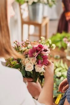 De handen van bloemist verzamelen huwelijksboeket. bloemist op het werk