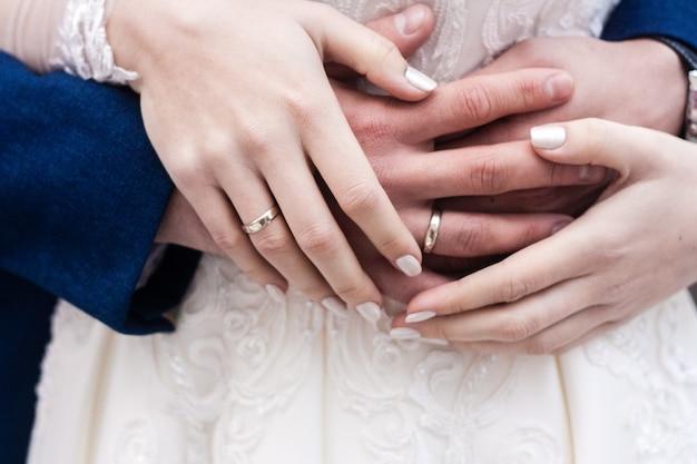 De handen van bruid en bruidegom met ringen sluiten omhoog
