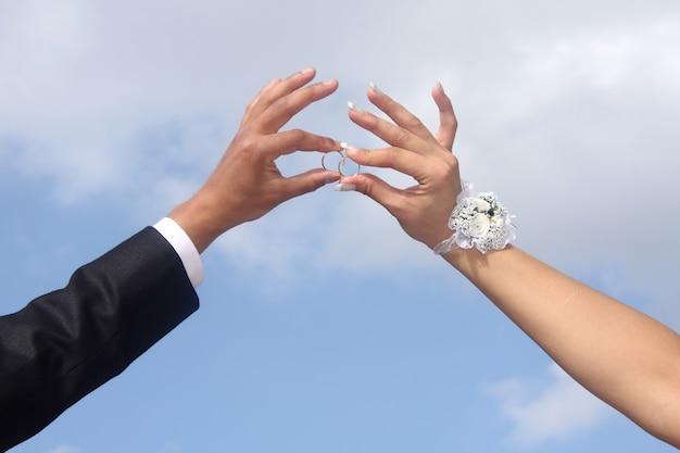 De handen van bruidegom en bruid houden trouwringen.