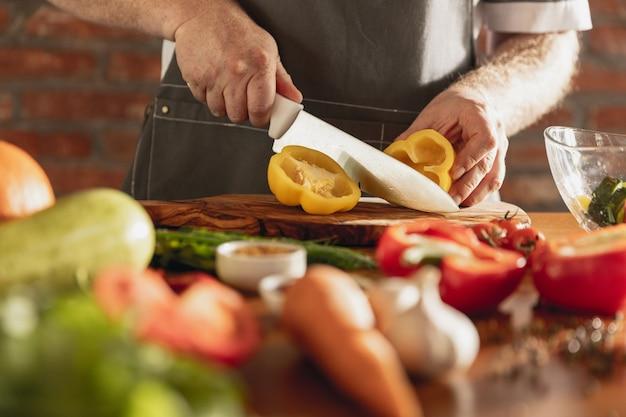 De handen van chef-kok die groenten snijdt in zijn keuken