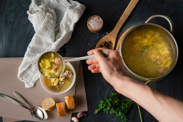 De handen van chef-kok gieten verse hete soep in een witte lege kom, voedselvoorbereidingen
