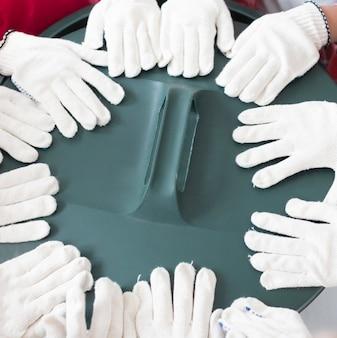 De handen van close-upkinderen met chirurgische handschoenen