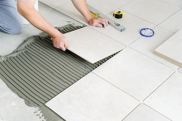 De handen van de arbeider leggen de keramische tegel op de vloer.