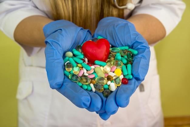 De handen van de arts houden verschillende pillen geïsoleerd op een green