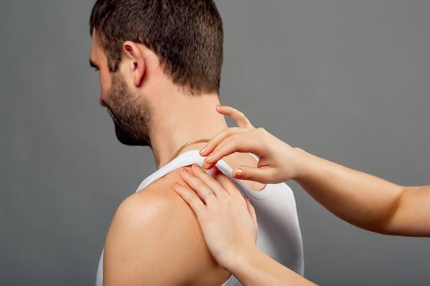 De handen van de arts onderzoeken de man met pijn in de schouder op grijs