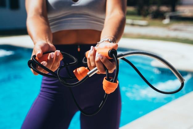 De handen van de atleet vrouw die elastische band