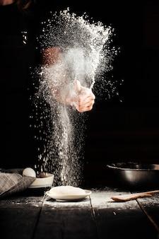 De handen van de bakker besprenkelen met de voorbereiding van de bloempizza
