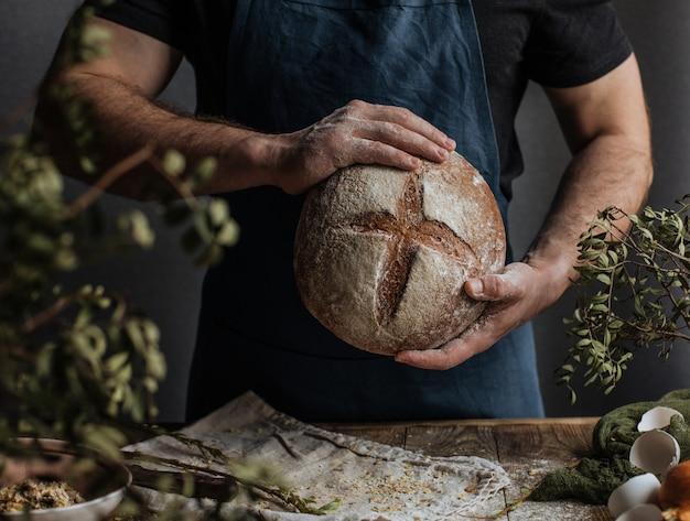 De handen van de bakker houden een brood van roggebrood boven een houten tafel.