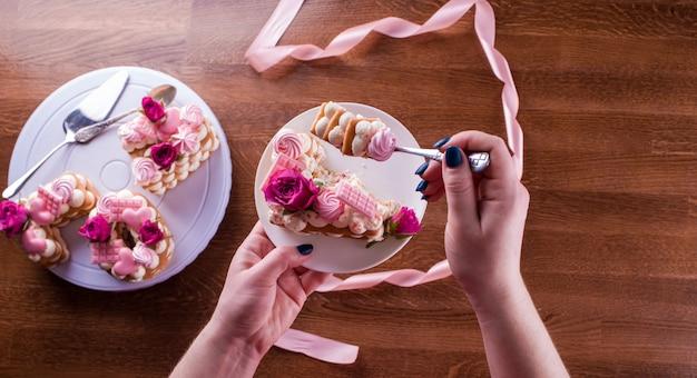 De handen van de banketbakker met een delicate en heerlijke taart van letters. taart met levende bloemen, witte chocolade, beas. handen van een gebakjechef-kok, die dessert inpakken.