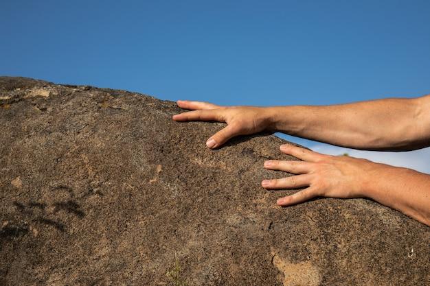 De handen van de bergbeklimmer op houvast op blauwe hemelachtergrond.