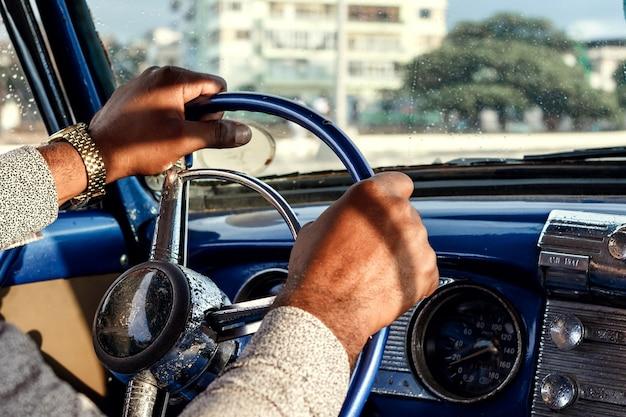 De handen van de bestuurder op het stuur van een retro auto