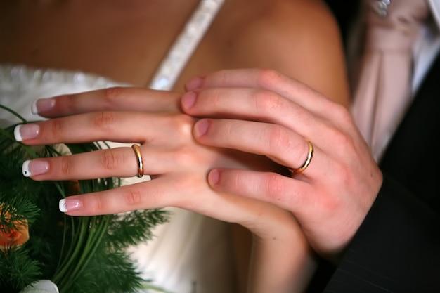De handen van de bruid en bruidegom met de ringen
