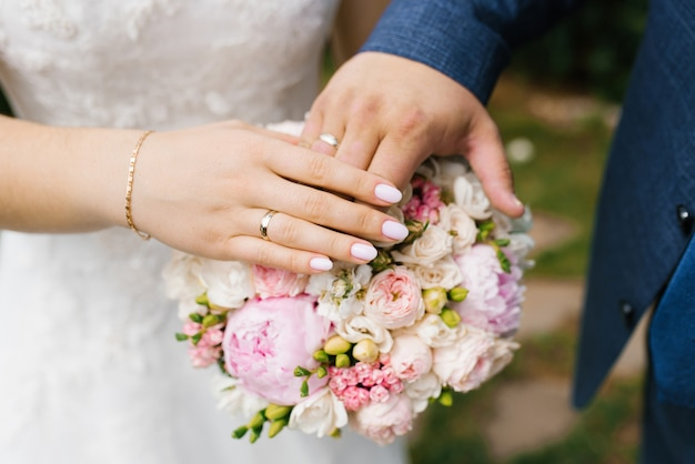 De handen van de bruid en bruidegom met trouwringen liggen op het huwelijksboeket van bloemen