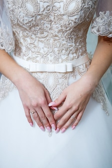 De handen van de bruid gevouwen op een witte trouwjurk