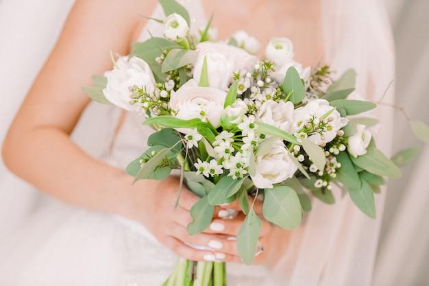 De handen van de bruid houden mooi bruids boeket