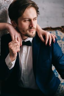 De handen van de bruid liggen op de schouders van de bruidegom