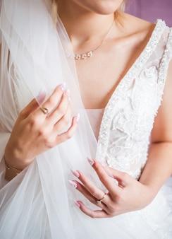 De handen van de bruid met gouden trouwring met een diamant. voorbereidingen van de bruid. huwelijksochtend. sieraden. manicure dichte omhooggaand. verloving. het knoopsgat met bloemen.