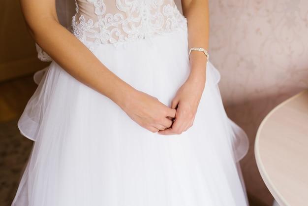 De handen van de bruid op de achtergrond van haar witte trouwjurk