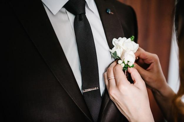 De handen van de bruid zet de bruidegom op de jas een bruiloft corsages. bruiloft concept.