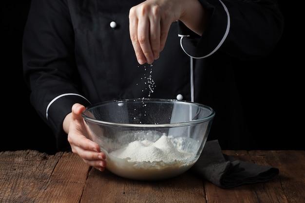 De handen van de chef bestrooit overzees zout op ruw deeg.