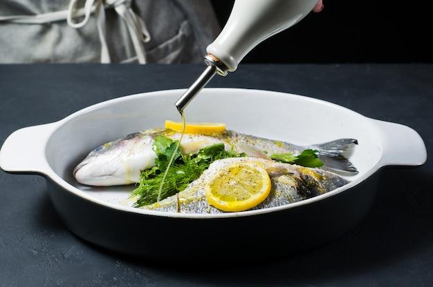 De handen van de chef drenkten dorado-vis met olijfolie.