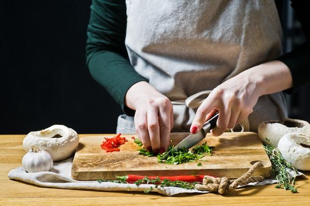 De handen van de chef snijden de chili-peper