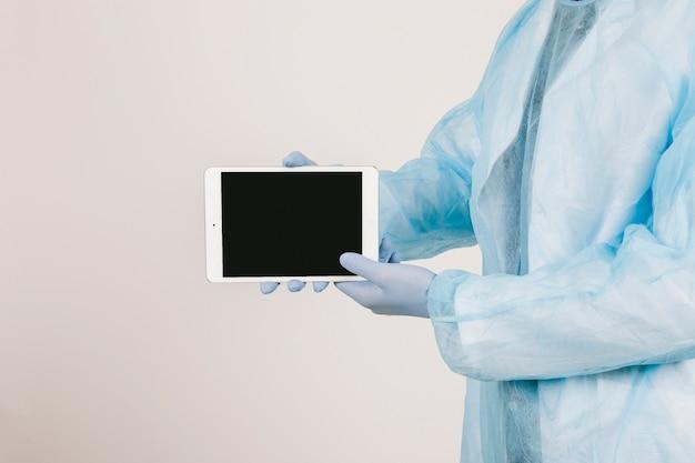 De handen van de chirurg tonen het scherm van de tablet