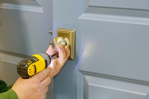 De handen van de close-uptimmerman met deurslot tijdens de installatie van het slotproces