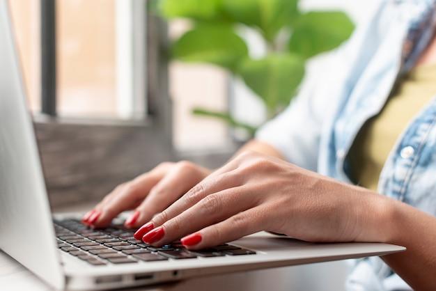 De handen van de close-upvrouw op laptop