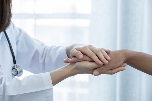 De handen van de dokter hielden de hand van de patiënt vast ter aanmoediging en legden de resultaten van het gezondheidsonderzoek uit.