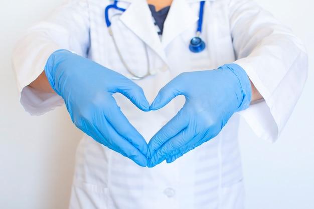 De handen van de dokter tonen gevouwen handen tot een hart. medische handschoenen op handen ter bescherming tegen infectie.