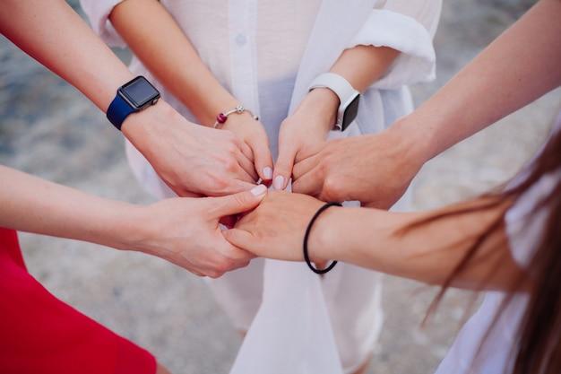 De handen van de drie meisjes zijn samengevoegd