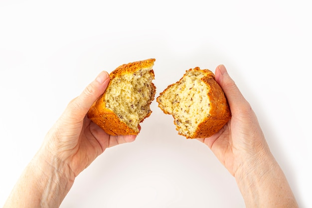 De handen van de elderyvrouw houden (breken) klein vers gebakken eigengemaakt volkorenbrood op witte achtergrond. helpend handconcept, omhoog sluit