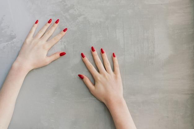 De handen van de geïsoleerde vrouw met rode spijkers voor een grijze muur