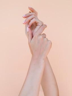 De handen van de gevoelige vrouw met roze vingernagels
