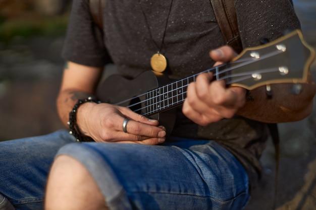 De handen van de jonge man spelen de zwarte ukelele zittend op een rots het concept van creativiteit van hoge kwaliteit...